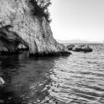 rocky cliff and cave with sea water in black and white