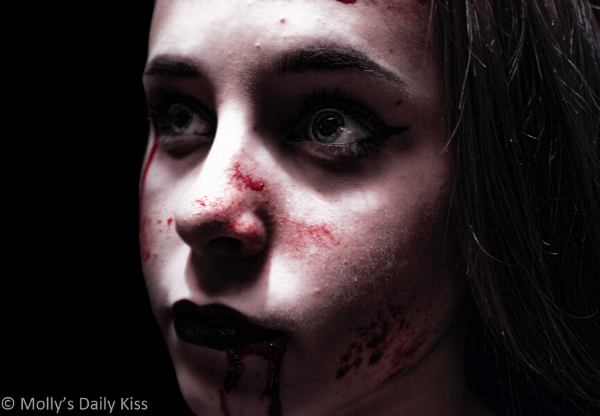 Girl vampire with blood on her face and lips. Blood drinkers