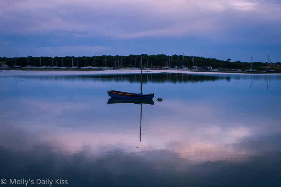 Lone sailing boat moored on very still water in Yarmouth Isle of Wight