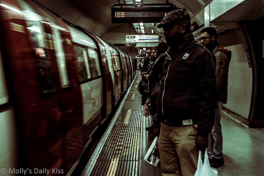 people waiting on the pplatform underground as tube train arrives