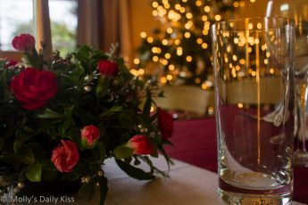 Christmas table flower decorations with bokeh christmas tree in the backgroun