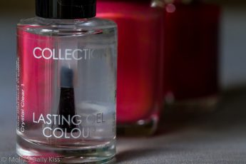 bottle of Clear nail polish with red nail polish bottles behind it
