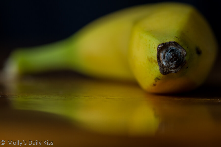 Macro shot of end of Banana reflected in table top
