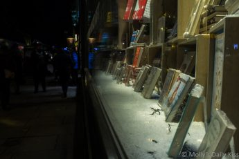 Reflection of people on the street in London book shop window that contains books which are silent voices