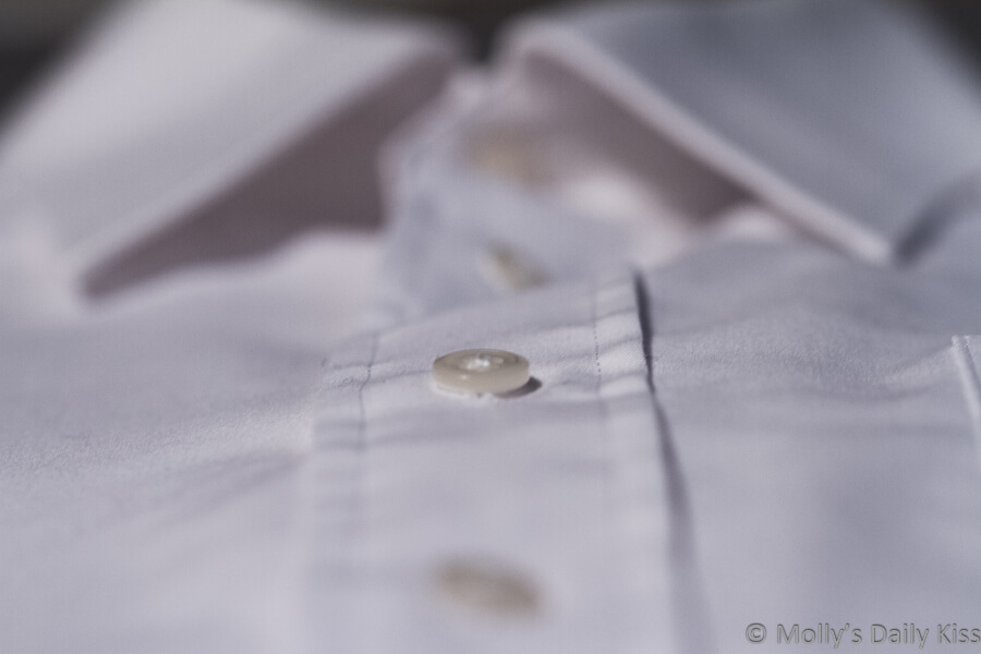 Macro short of button on white fitted shirt