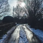 Snow lining either side of country lane with weak sunshine coming through the trees