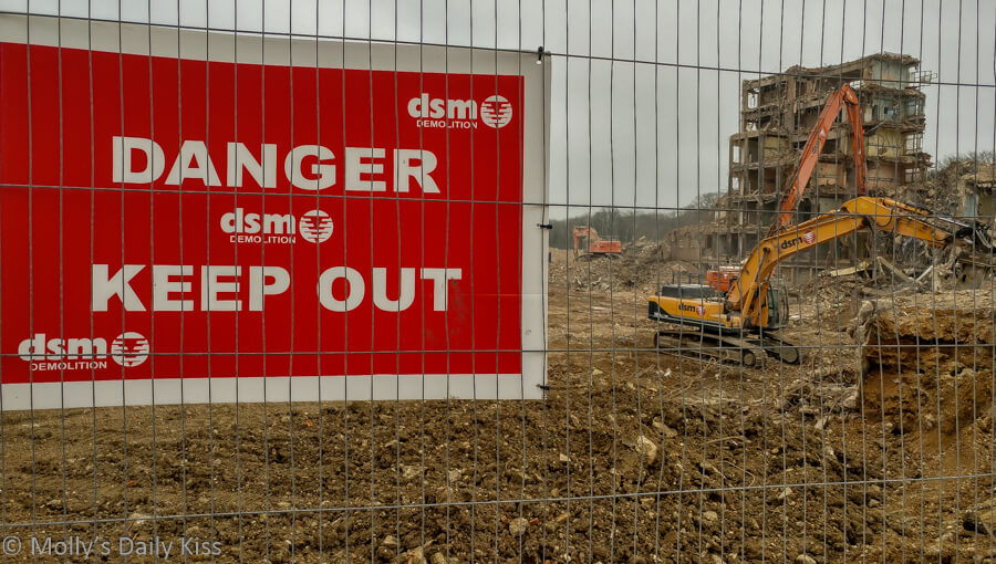 Danger keep out building site sign with digger in the background
