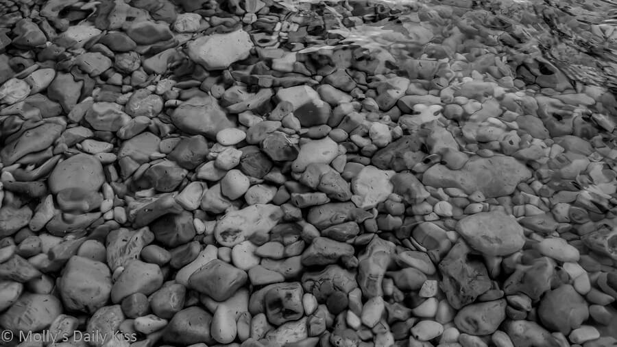 pebbles on the shore with the water coming over them in black and white
