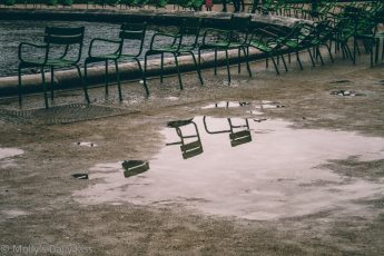 Chairs reflected in puddle in Paris