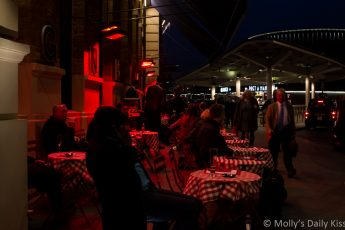 People sitting outside under heat lamps at Kings Cross station in London