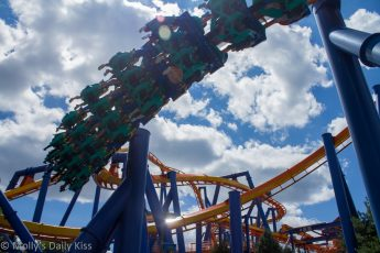 Rollar coaster is like hills and valleys with blue sky behind it