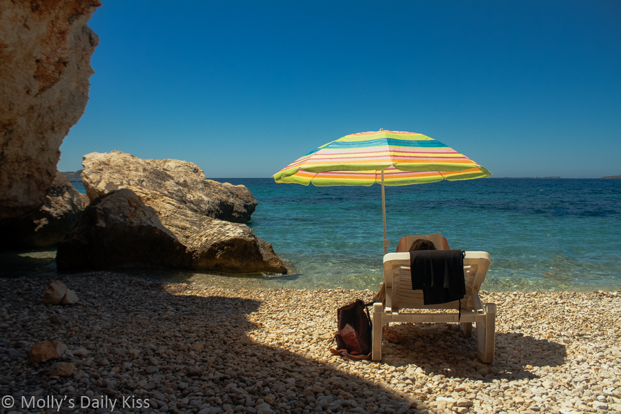 woman sitting on sun lounger under umbrella reading a book on the beach