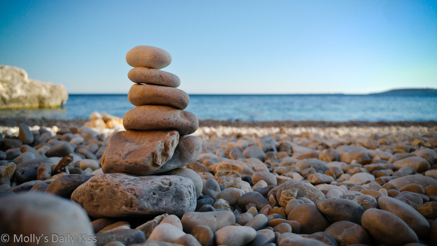 tower of pebbles on the beach with blue ocean in the background. Elemental