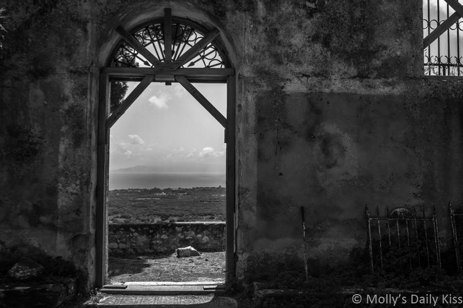 Abandoned church in Kefalonia greece, looking out through the door at the view beyond edited in black and white