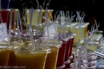 rows of fruit juices in cups with straws in Borough Market