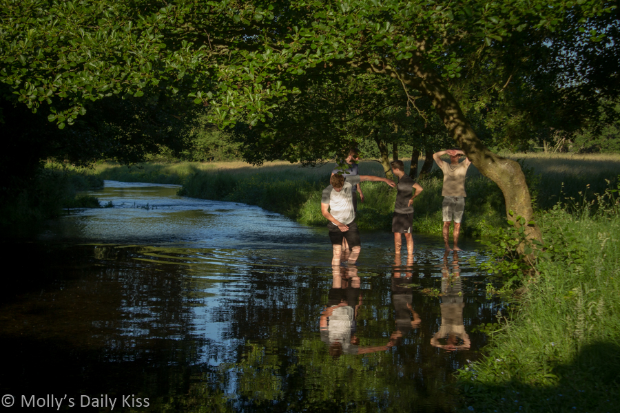 boys reflected in the water in the stream