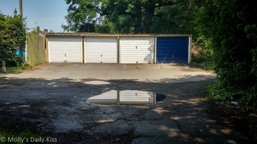 Reflection of garages in a puddle