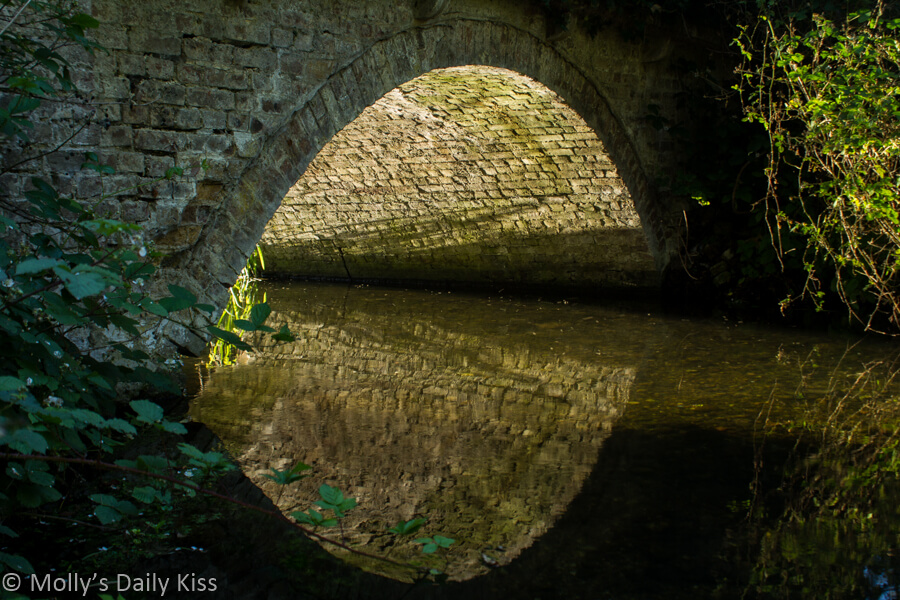 Roof of brick build tunnel reflected in the stream that runs through it