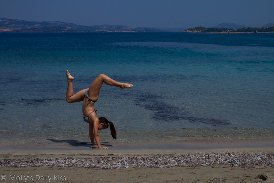 Young girl upside down doing hand stand on the beach