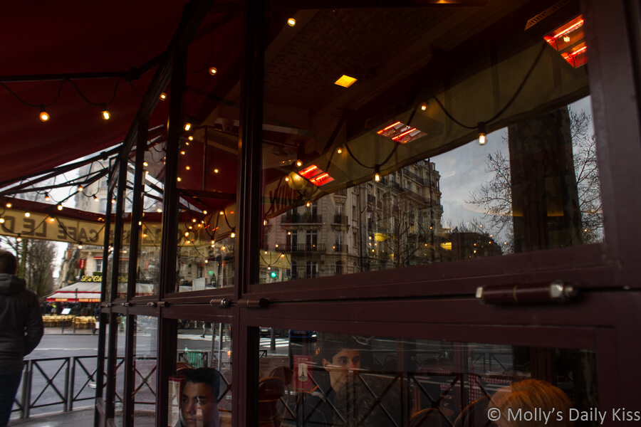 reflections of lights and other buildings in the window of a paris cafe