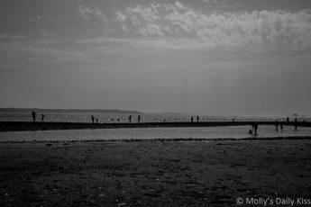 black and white of beach looking out over The Solent with silhoutte people