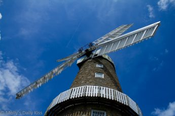 Looking up at windmill surrounded by bright blue sky