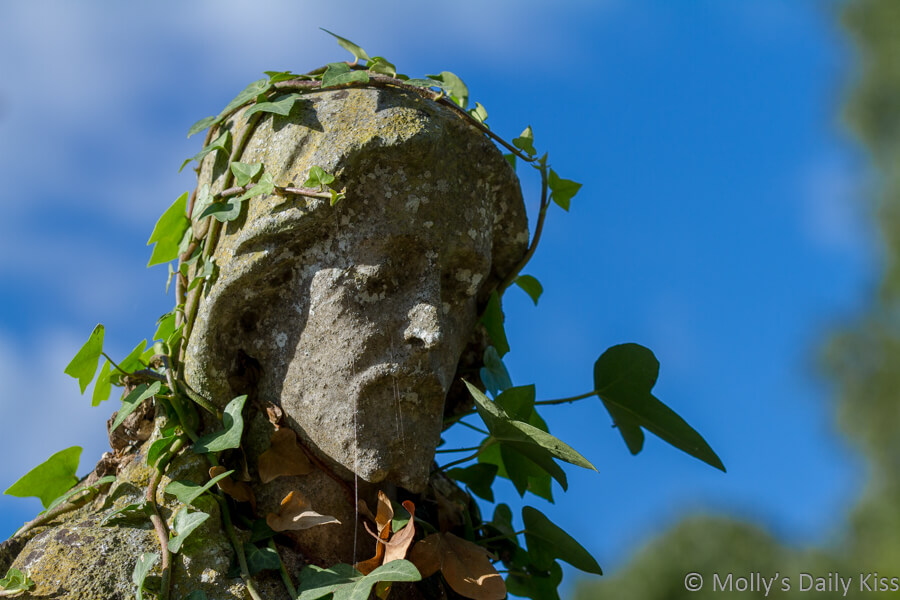 stone Sculpture of Jesus in Southampton Cemetary with ivy growing over it and blue sky background