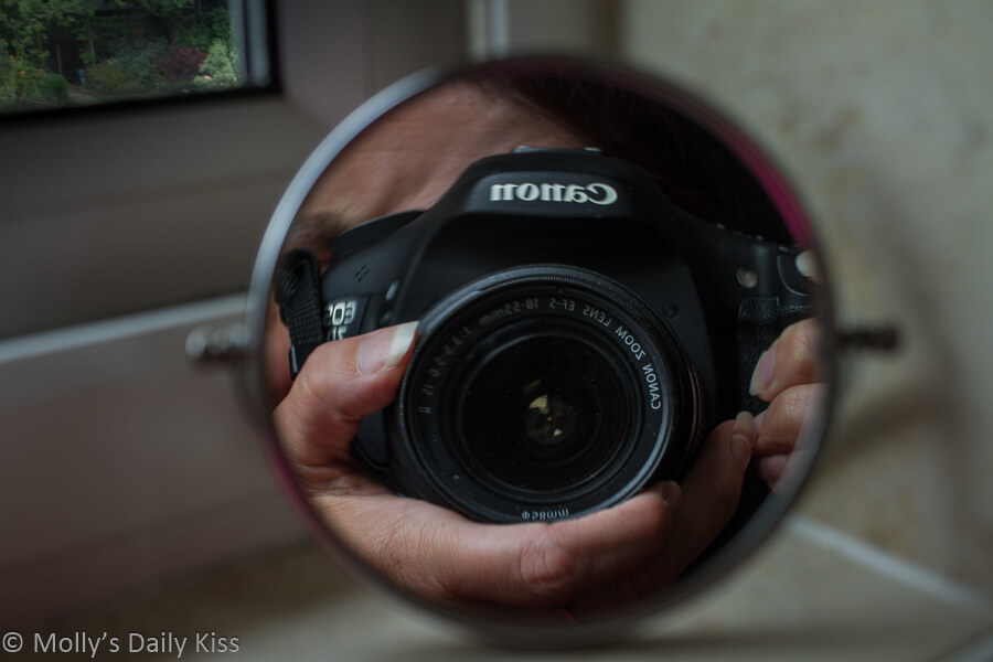 self portrait of molly holding camera shooting into small round mirror