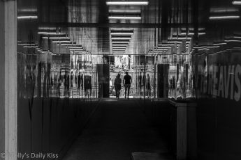 couple holding hands walking through tunnel that is reflecting them on both sides edited in black and white