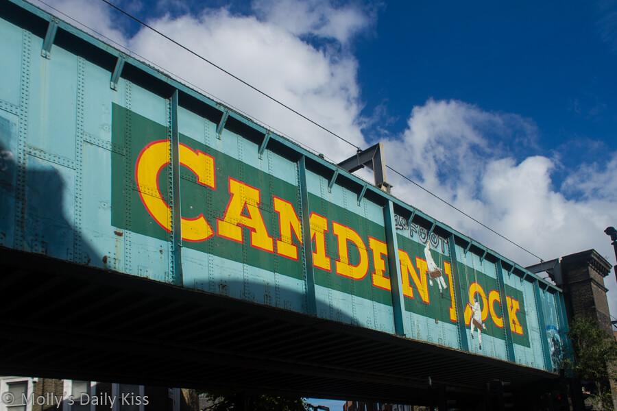 Camden market bridge with blue skies above it