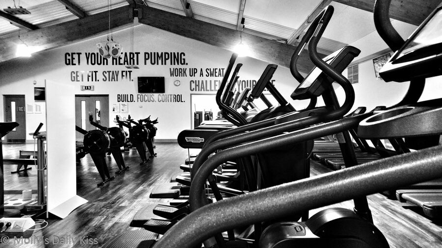 Black and white image of the gym with rowing machines, bikes and motivational writing on the wall