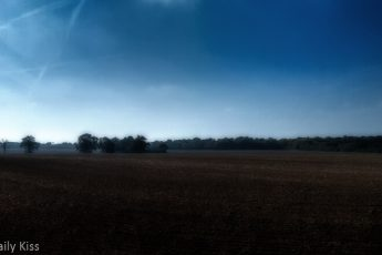 plouged field with morning mist and bright blue sky