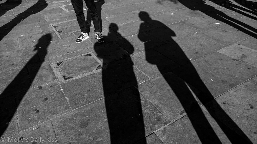 Long shadows of people on pavement