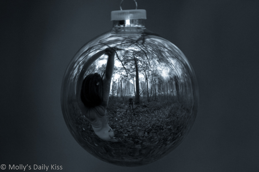 Molly renaked reflected in Christmas bauble hanging in the woods