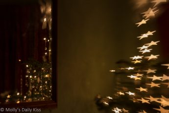Relfection of Christmas tree in mirror with tree showing bokeh stars