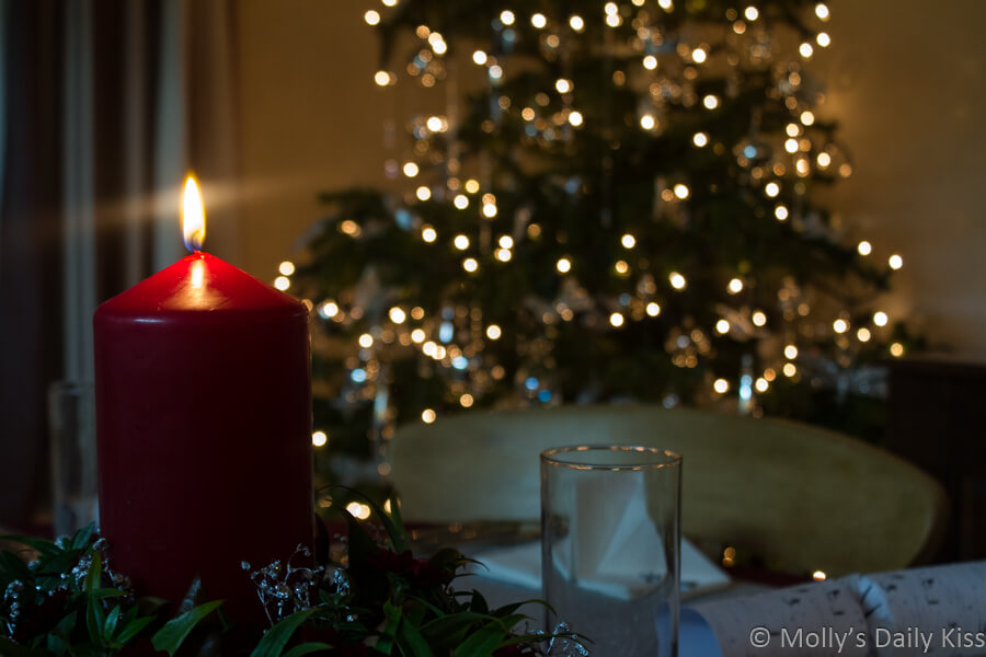 Red candle lit on Christmas table in front of Christmas tree