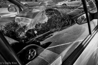 reflection of trees and other car in the window of a car in black and white