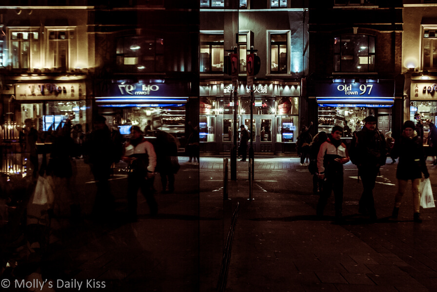 people reflected in shop window in london at night