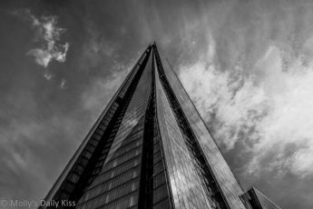 Looking up the Shard landmark in london to whispy clouds in the sky in black and white