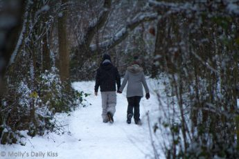 Couple walking through snow in woods
