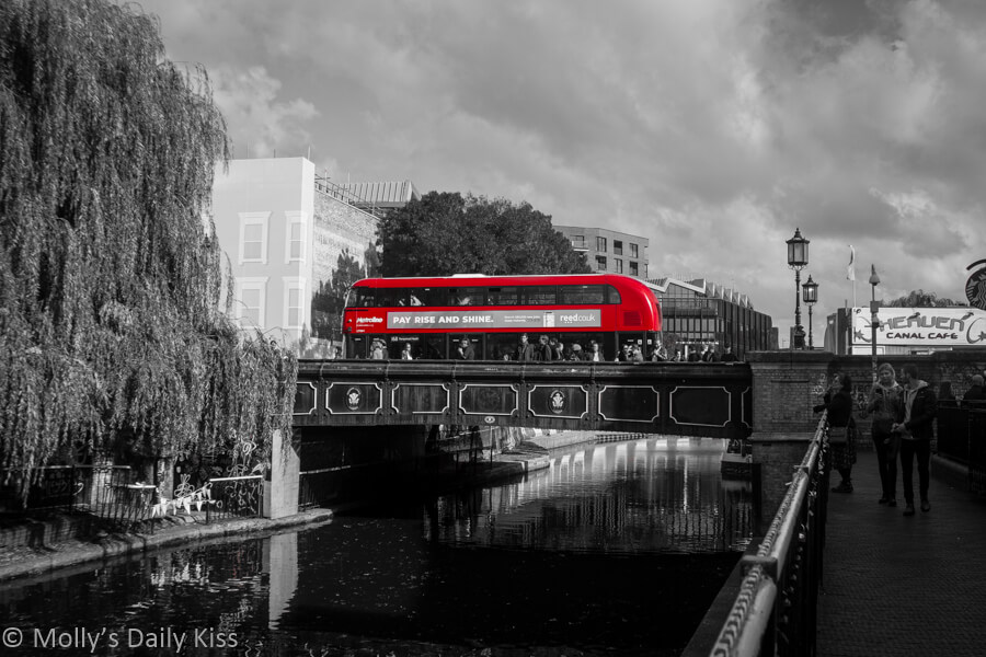 red bus going over canal bridge in camden