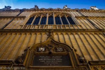 Looking up the front of the Bodleian library to blue sky
