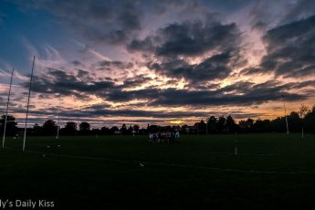 Rugby team on pitch beneath amazing sunset