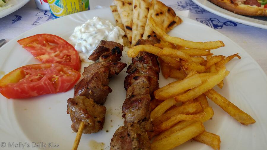 Plate of greek souvlaki, chips, pitta bread good food