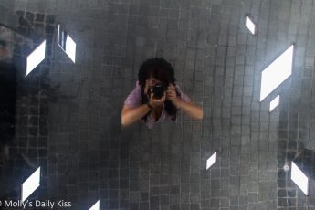 Molly looking up at mirror ceiling taking picture of herself