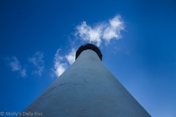 looking up a lighthouse to bright blue skies