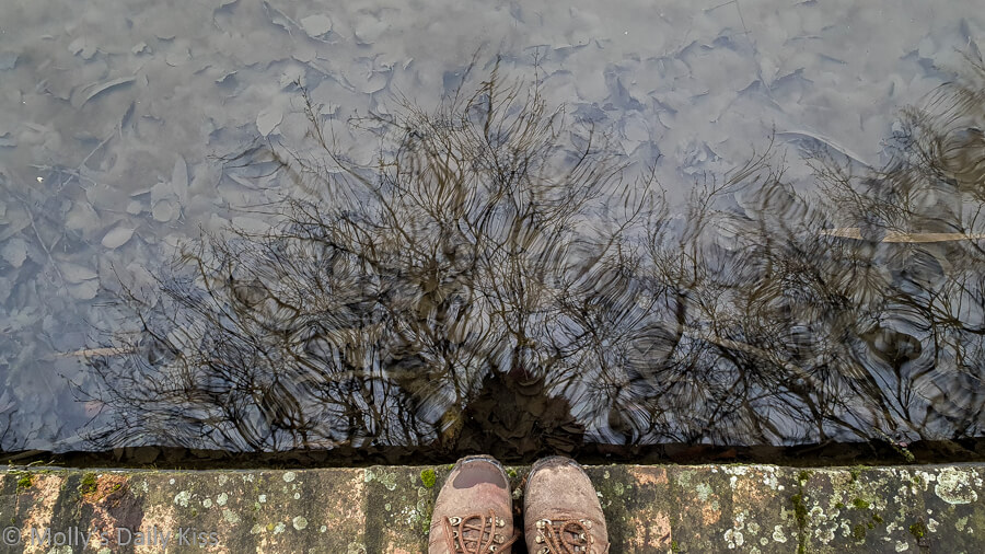 self portrait of my boots on the edge of pond and me reflected in the water