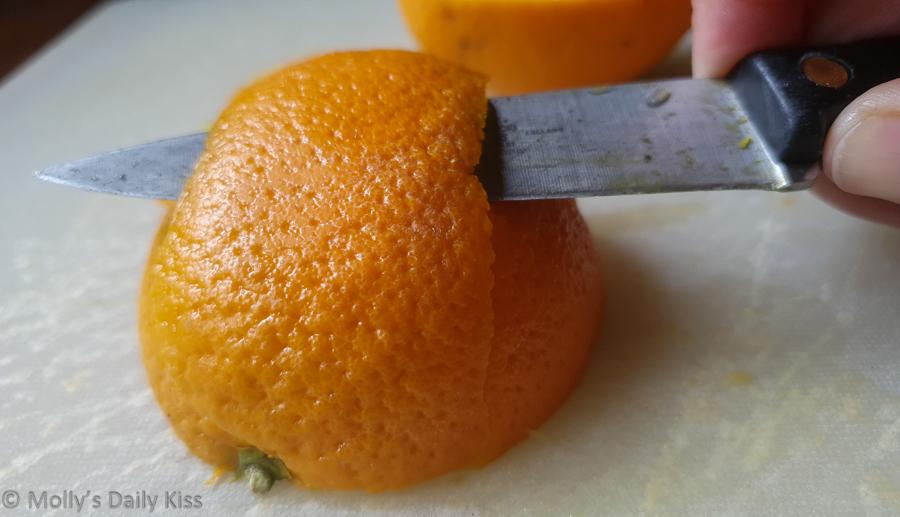Knife slicing into orange