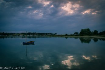 Dignity, little blue boat moored in water with clouds relfected