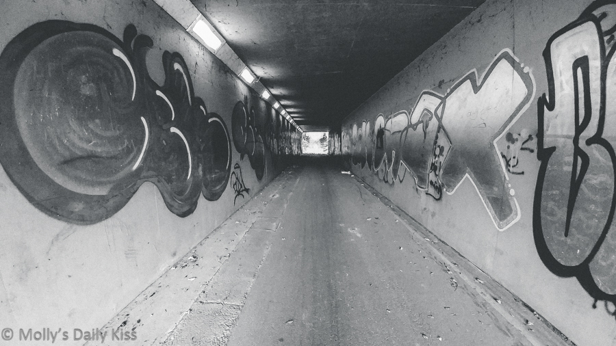 black and white of underpass tunnel with graffiti on the walls